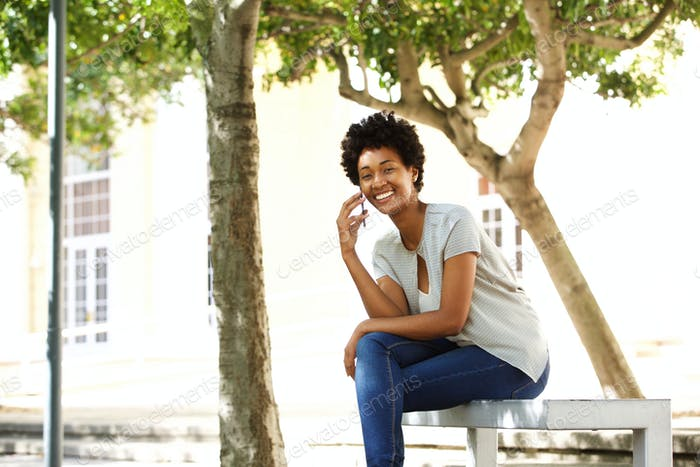 Happy african woman on a bench using mobile phone