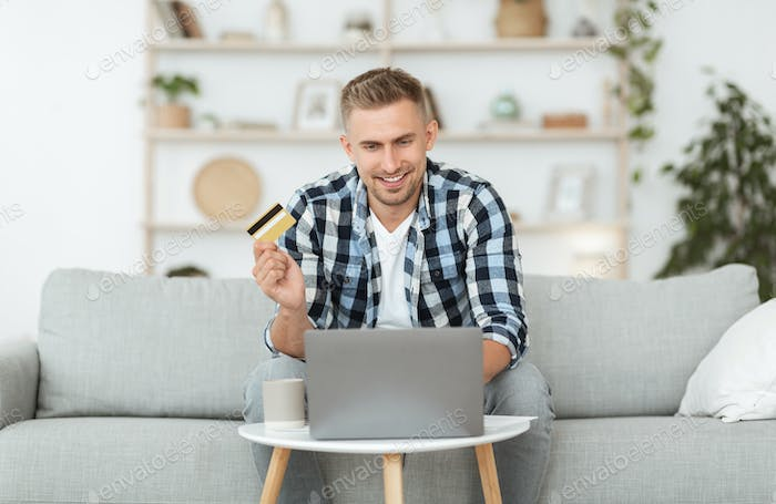 Cheerful adult guy using laptop and credit card