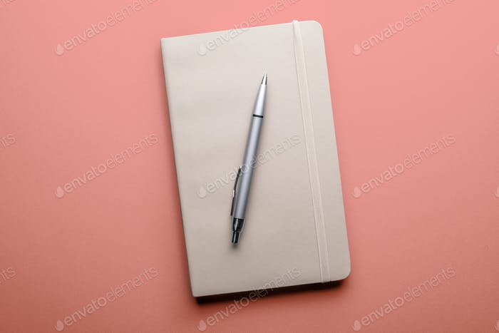 top view of old open book with fountain pen on pink background