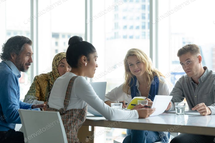 Front view of diverse business people discussing over document at table in a modern office