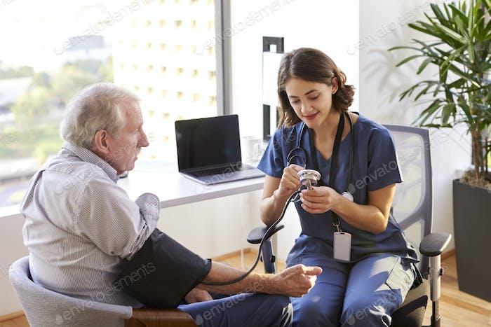 Nurse Wearing Scrubs In Office Checking Senior Male Patients Blood Pressure