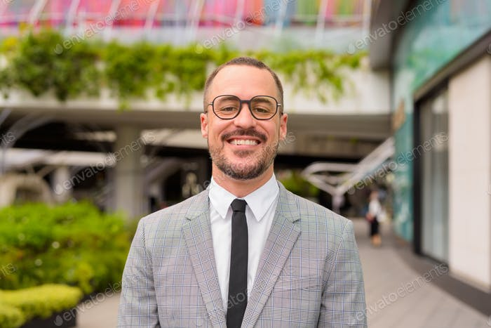 Happy Hispanic bald bearded businessman with eyeglasses smiling outside modern building