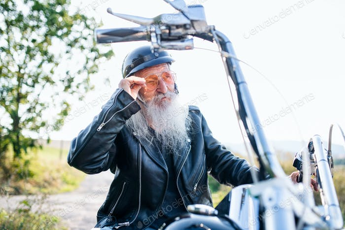A senior man traveller with motorbike in countryside
