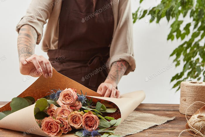 Gardener girl make bouquet for a holiday from living coral roses and branches of green leaf on a