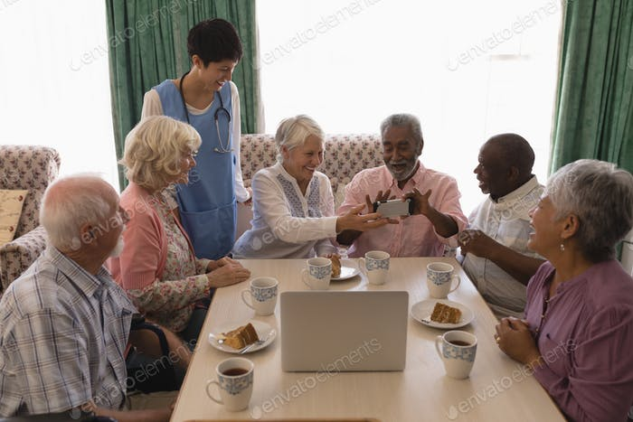 Front view of active senior people holding mobile phone and showing funny screen at nursing home