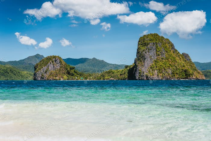 El Nido, Philippines. Crystal clear blue water lagoon and private Malapacao island in background