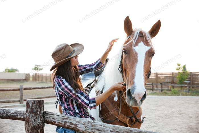 Beautiful young woman cowgirl with horse in village