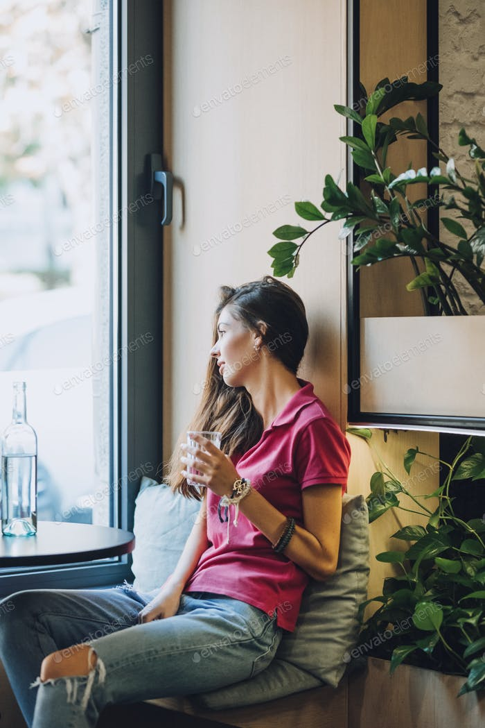 Drinking more water, drink water reminder, keep water tracker. Brunette girl drinking water from a