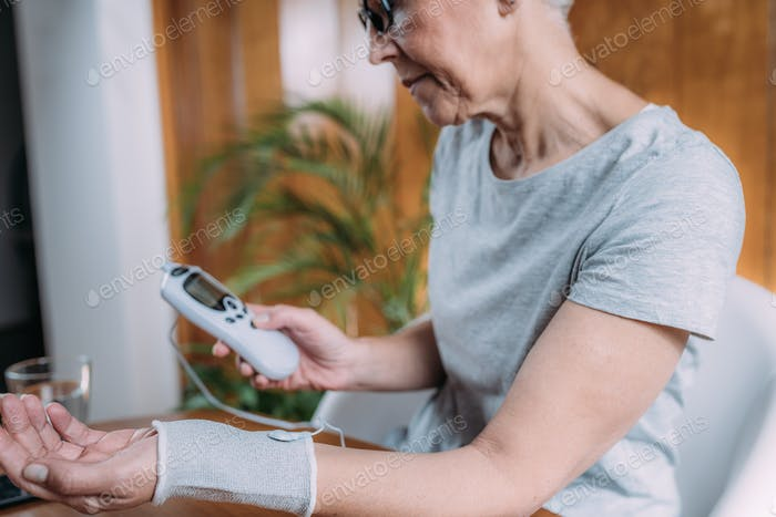 Senior Woman Doing Wrist Joint Physical Therapy with Conductive TENS Electrode Sock