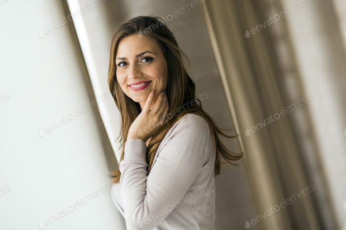 Beautiful and successful brunette posing in front of a window