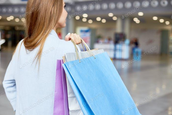 Junge Frau hält Einkaufstaschen in Mall