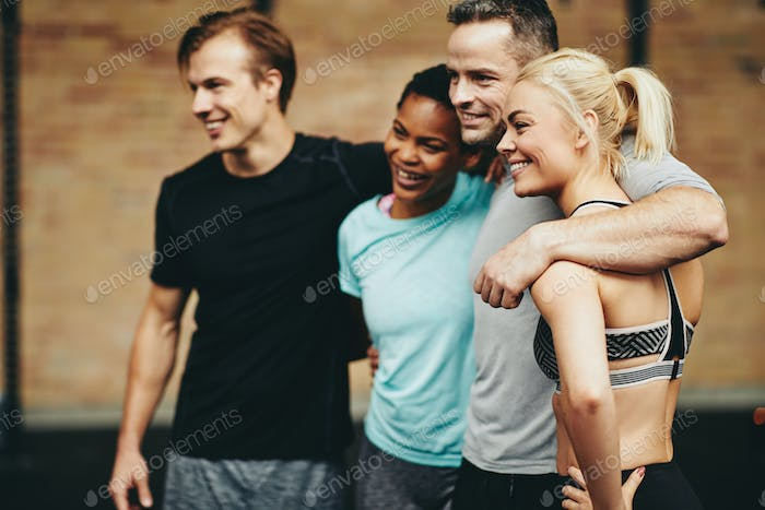 Diverse friends smiling in a gym after working out class