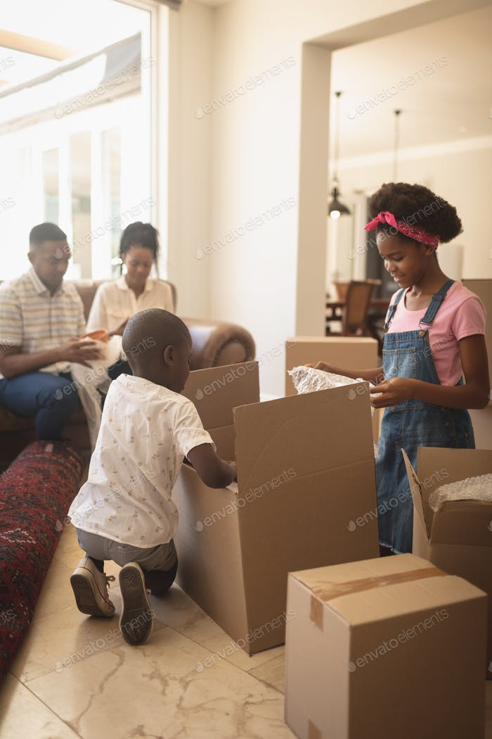 Children unpacking their belongings and parents sitting on sofa at home