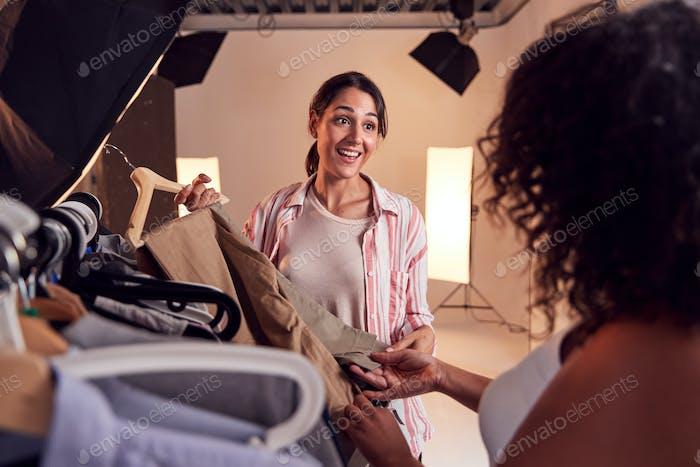 Estilista discutiendo armario con fotógrafa Mujer en la moda disparar en Estudio