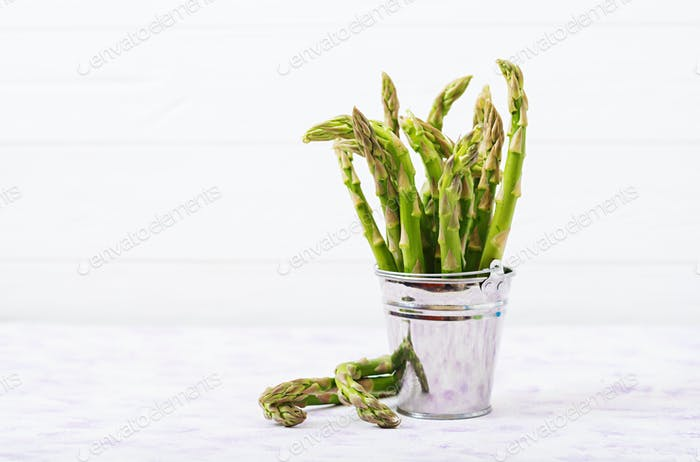 Fresh asparagus in bucket on light  background.