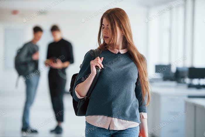 Mirando cuidadosamente hacia atrás. Grupo de jóvenes caminando en la oficina en su tiempo de descanso