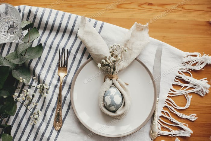 Modern natural dyed pink easter egg on napkin with bunny ears, flowers on plate and cutlery