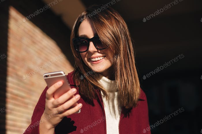 Young smiling lady in sunglasses standing on street and happily using her mobile phone