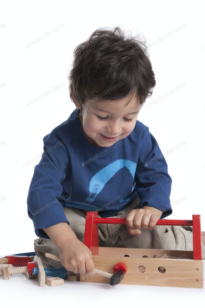 Two year old boy is playing with wooden tools