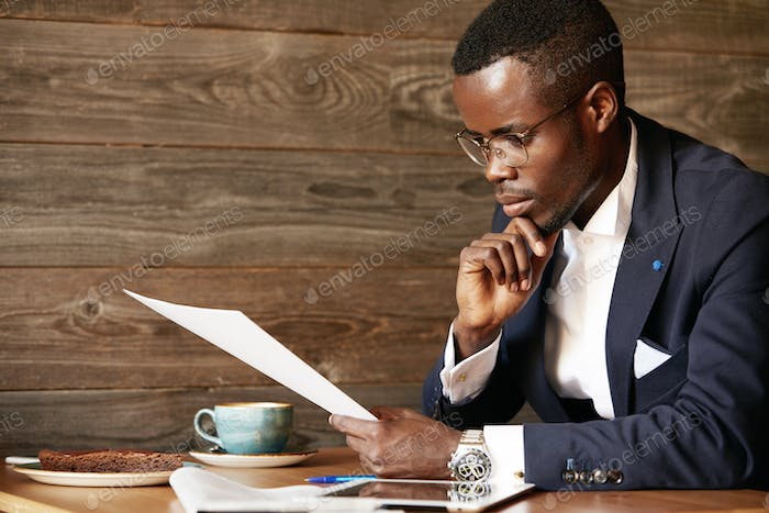 Portrait of young successful African businessman in formal wear sitting at the wooden table at a caf