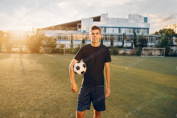 Male soccer player poses with ball in hands