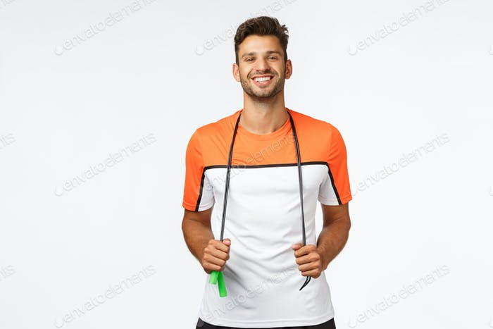 Fröhlicher, gesunder gutaussehender Mann in Sportbekleidung hält Seilspringen um den Hals, Lächeln erfreut und