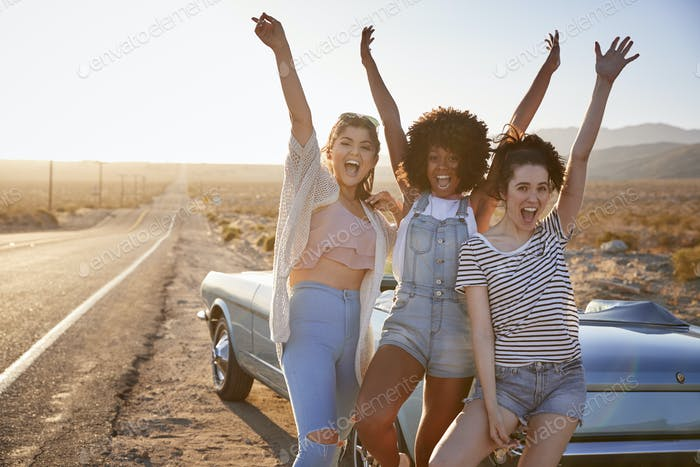 Portrait Of Female Friends Enjoying Road Trip Standing Next To Classic Car On Desert Highway