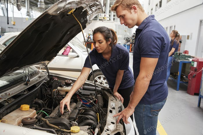 Two apprentice mechanics looking at the engine in a car