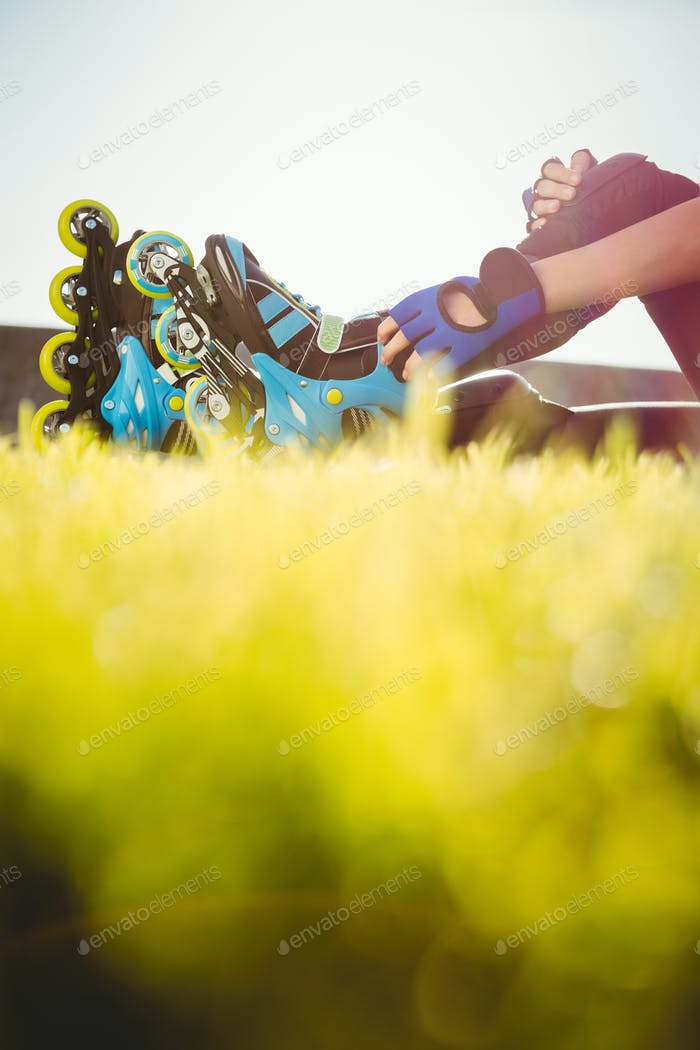 Woman wearing inline skates sitting in grass at promenade
