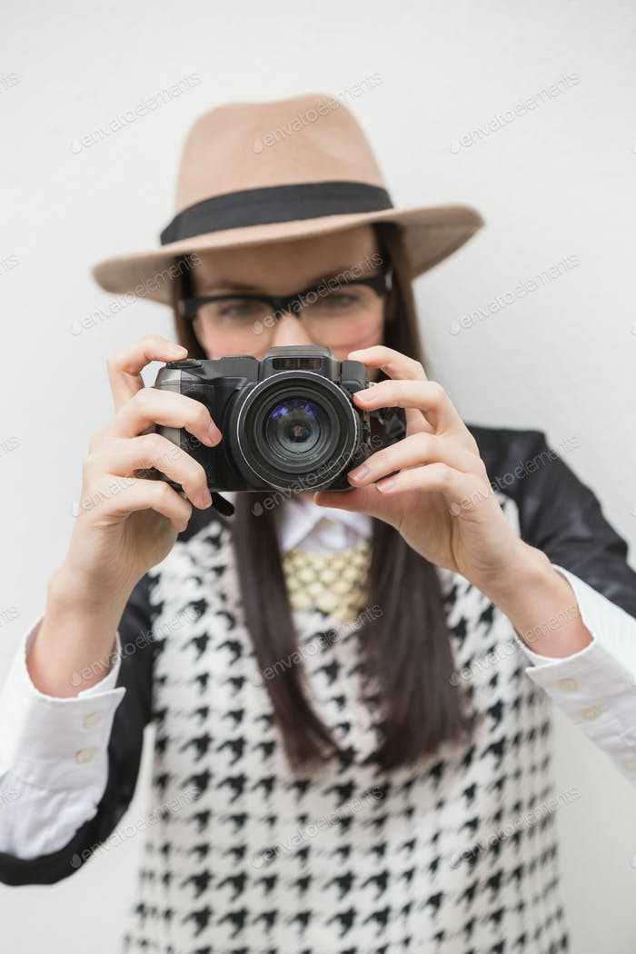 Pretty hipster taking a photo against bleached wooden planks