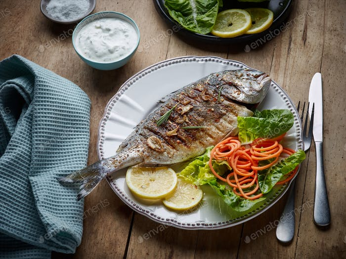 grilled fish on wooden kitchen table