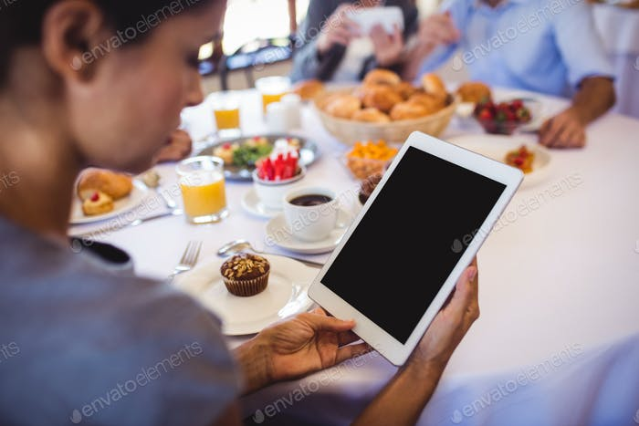 Close-up of businesswoman using digital tablet in restaurant