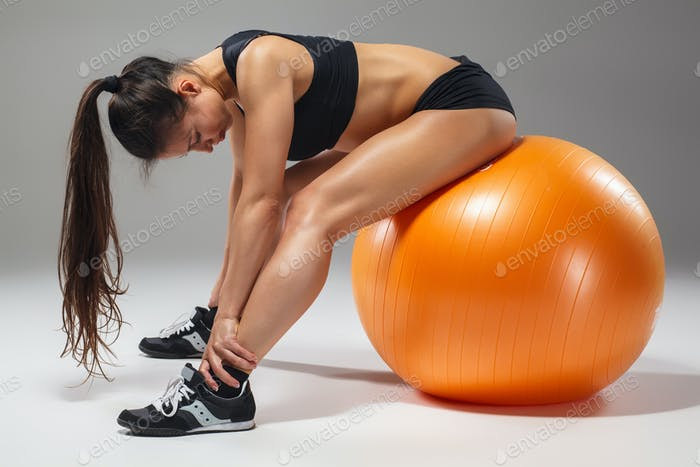 The young, beautiful, sports girl doing exercises on a fitball