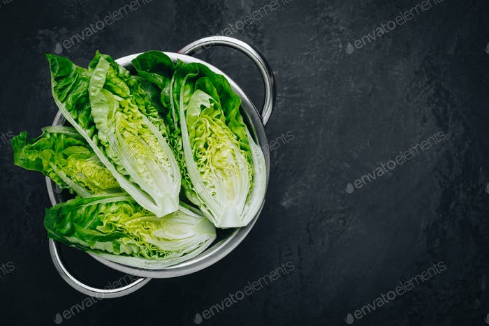 Fresh Green Romaine Lettuce for Caesar Salad on dark stone background.