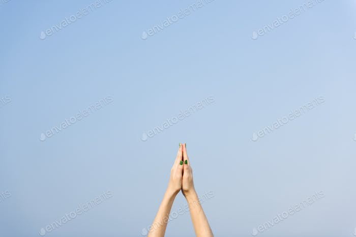 Praying hands pointed towards the sky, yoga excercise and stretching concept