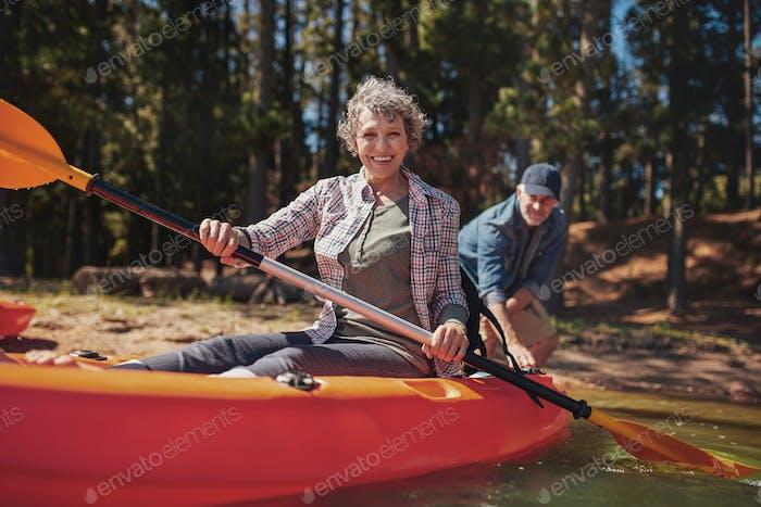 Glückliche Seniorin in einem Kajak am See