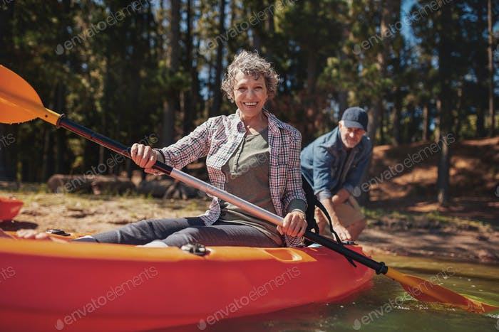 Happy senior woman in a kayak at the lake