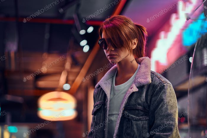 Stylish redhead girl standing in the night on the street.