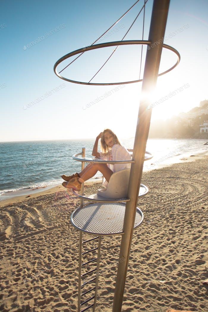 Hermosa modelo en la playa al atardecer