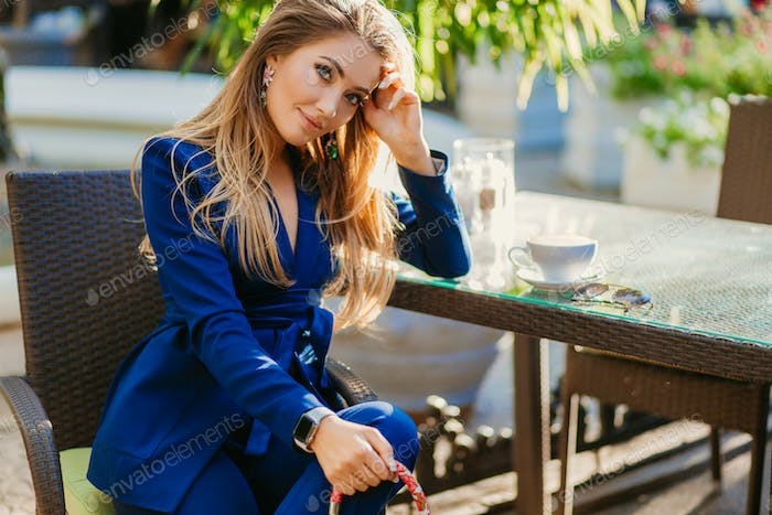 attractive woman dressed in blue elegant suit sitting in cafe in city street