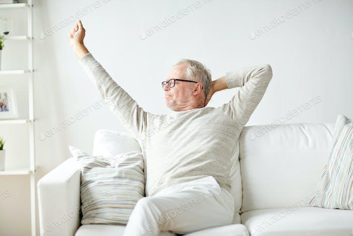 Hombre mayor en gafas Relajante en el sofá