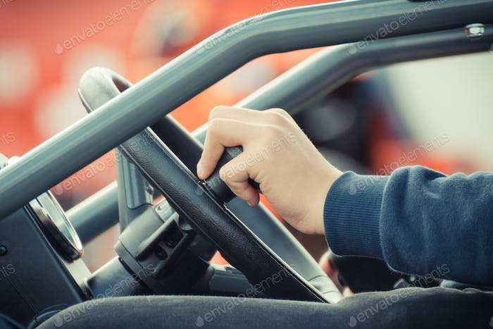 Man operating steering wheel in agricultural or industrial machine, detail of vehicle