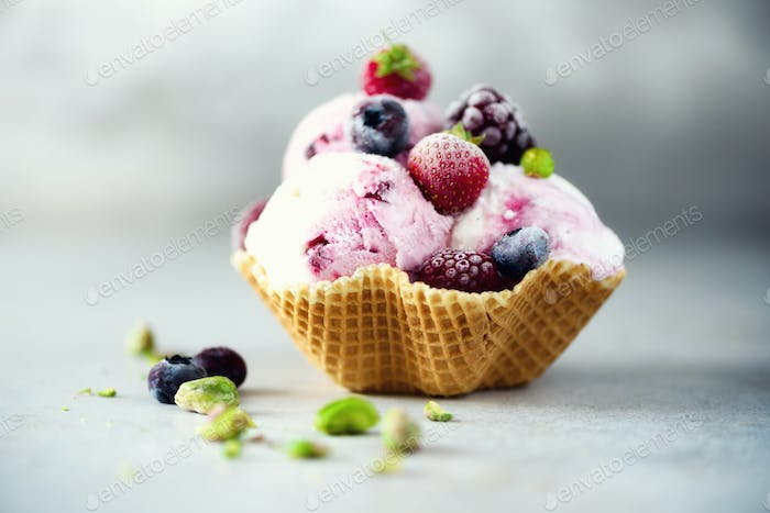 Pink ice cream with berries, strawberries, blueberries, raspberries, pistachios in waffle basket