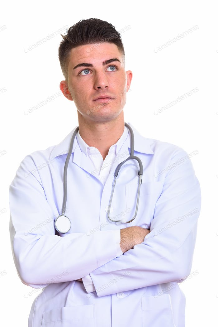 Studio shot of young handsome man doctor thinking with arms cros