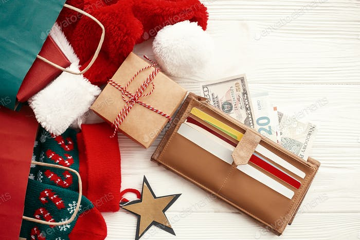 Credit cards and money in wallet, paper bags with clothes, stockings, gift boxes