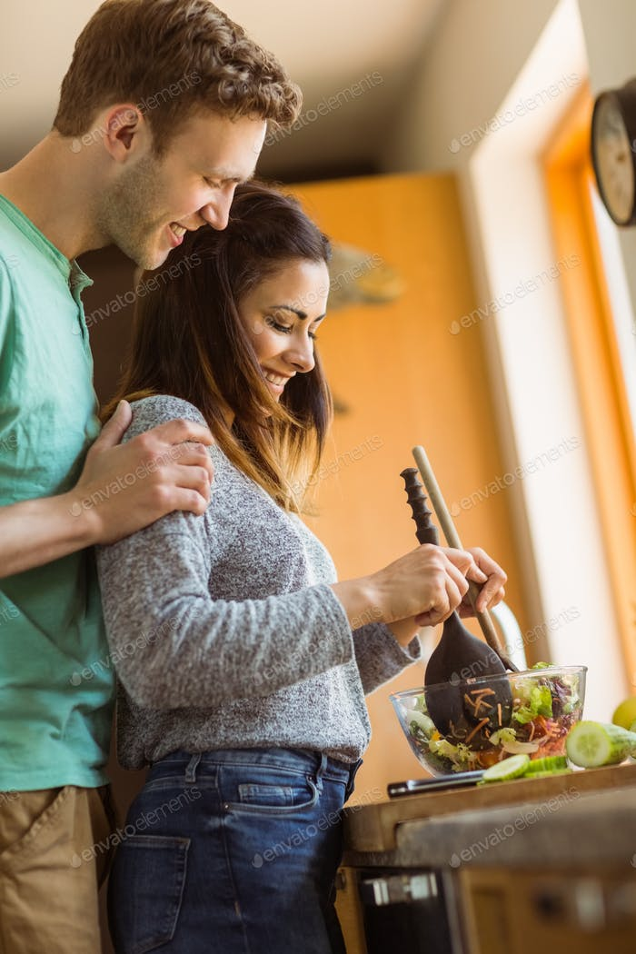 Cute couple making a salad at home in the kitchen