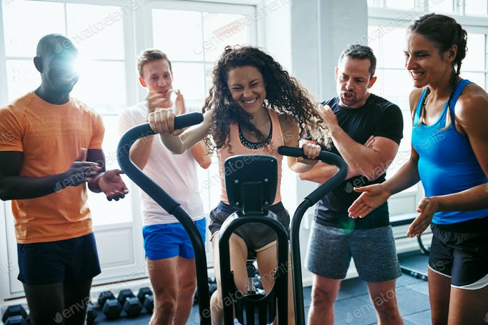 People supporting their friend riding a gym stationary bike