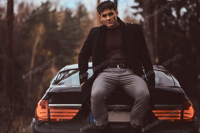 Stylish young man wearing a black coat standing next to a luxury car in the autumn forest