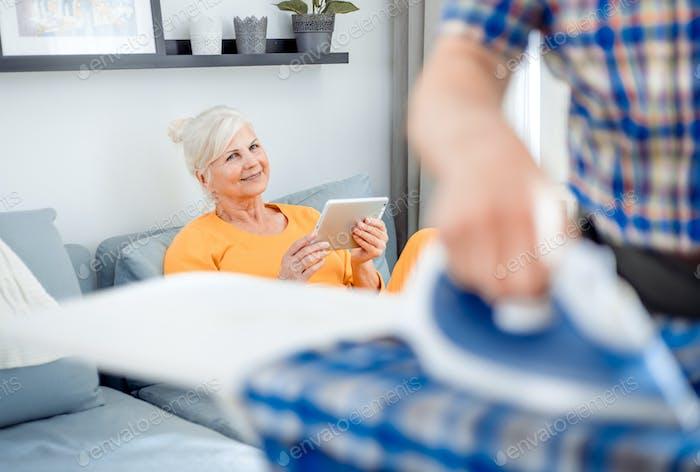 Esposa mayor mirando a su marido mientras él hacía las tareas domésticas con hierro y ropa