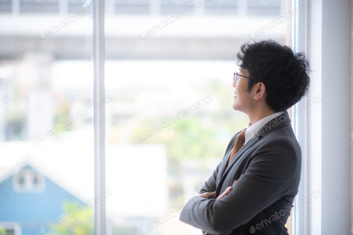 A young Asian businessman in a gray suit is looking out for good vision